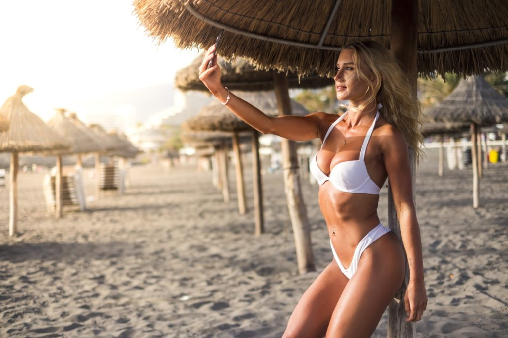 Beautiful caucasian attractive blonde girl at the beach during vacation taking selfie at the sunset - tourist and summer holiday concept for cute young woman in outdoor tropical resort